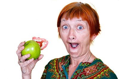 Old woman biting an apple